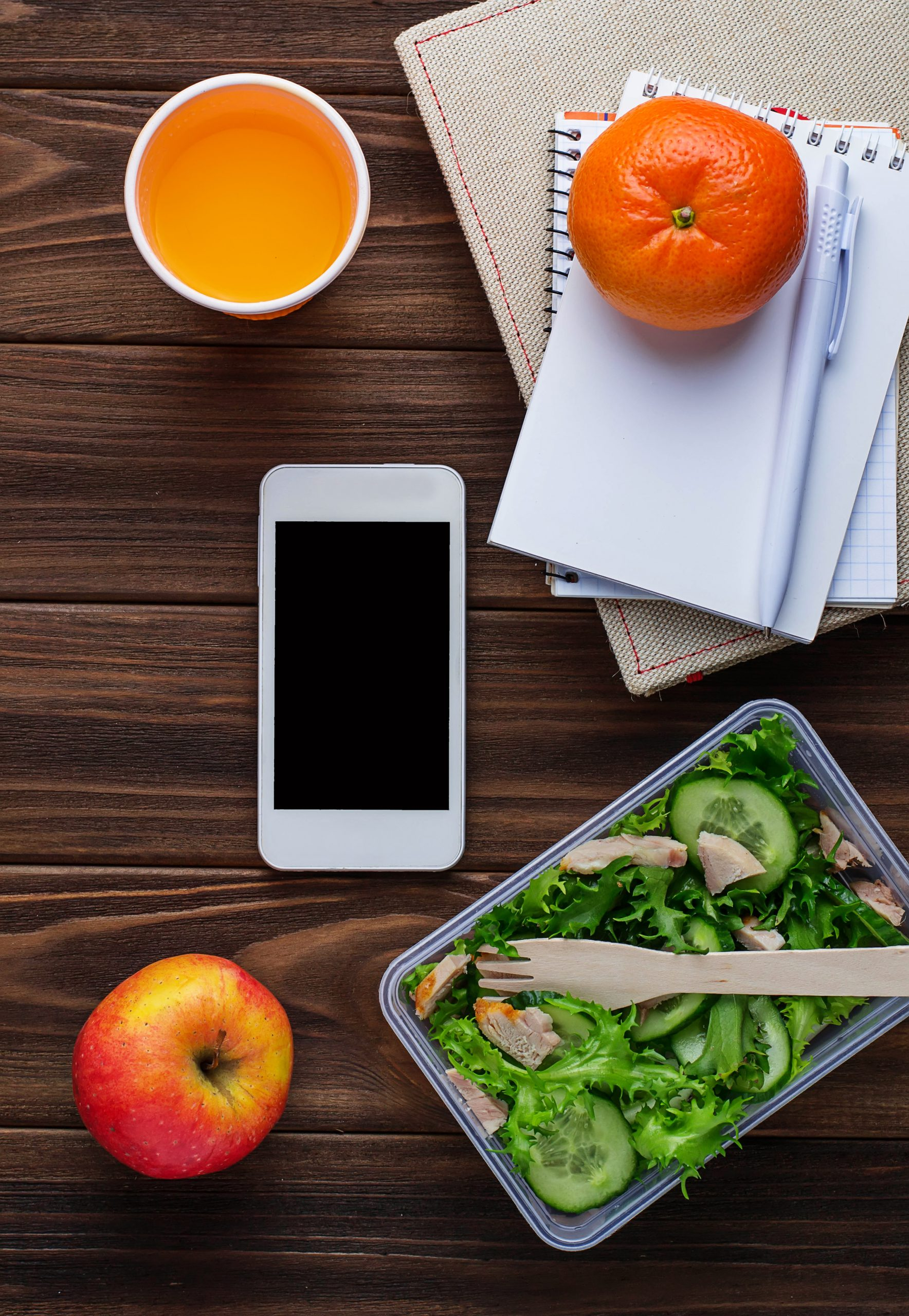 Lunch box with salad, notebook and phone